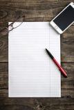 Papel de nota en blanco con la pluma en la tabla Imagen de archivo libre de regalías