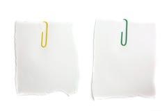 Papel de nota en blanco y paper-clip aislados en blanco Imagen de archivo libre de regalías