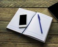 Papel de nota, lápis, tabuleta e telefone na mesa de madeira velha Imagem de Stock