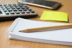 Papel de nota, lápiz, calculadora y teléfono móvil Fotografía de archivo