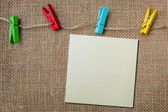 Papel de nota no fundo da textura do pano de saco com cl de madeira colorido Imagens de Stock