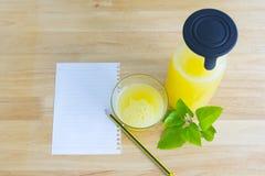Papel de nota, suco de abacaxi e folhas do verde colocados em Ta de madeira Imagem de Stock