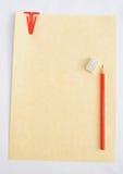 Papel de pergamino, clip de papel rojo y lápiz rojo. Fotos de archivo libres de regalías