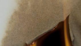 Papel de queimadura através do centro em um fundo preto filme