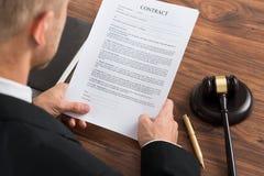 Papel del contrato de la lectura del juez Foto de archivo libre de regalías