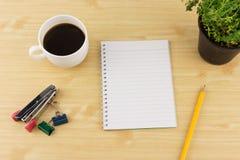 Papel del cuaderno con los lápices, el café, el tomillo en maceta, la grapadora y el paperclip en fondo de madera marrón de la ta Foto de archivo libre de regalías