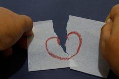 Papel del rasgón de la mano con símbolo del amor Imagenes de archivo