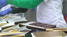 Papel dourado barras de chocolate envolvidas Processo de empacotar o chocolate na fábrica video estoque