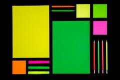 Papel e artigos de papelaria de néon no preto fotos de stock royalty free