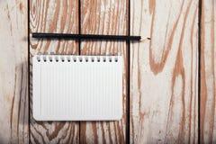 Papel e lápis vazios do livro de nota no fundo de madeira Foto de Stock Royalty Free