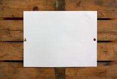 Papel em branco na parede de madeira Fotos de Stock