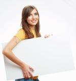Papel en blanco blanco del asimiento de la muchacha del adolescente. Demostración sonriente joven b de la mujer Fotografía de archivo