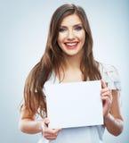 Papel en blanco blanco del asimiento de la muchacha del adolescente Demostración sonriente joven de la mujer Imagen de archivo libre de regalías