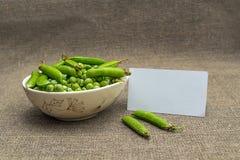 Papel en blanco blanco y guisantes verdes en un cuenco Fotografía de archivo libre de regalías
