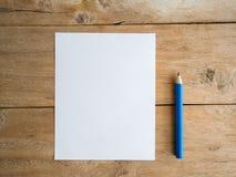 Papel en blanco con el lápiz en la tabla de madera Imagenes de archivo