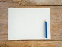 Papel en blanco con el lápiz en la tabla de madera Fotografía de archivo