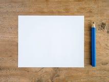 Papel en blanco con el lápiz en la tabla de madera Foto de archivo