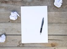 Papel en blanco con las bolas de papel arrugadas en la tabla de madera imagen de archivo libre de regalías