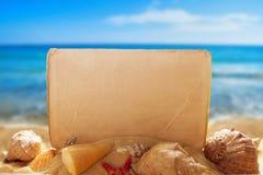 Papel en blanco con las conchas marinas en la playa Fotos de archivo libres de regalías