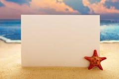 Papel en blanco con las estrellas de mar en la playa arenosa Fotografía de archivo
