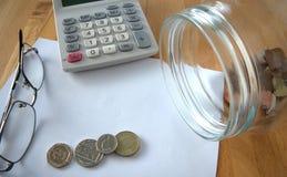 Papel en blanco con las monedas y la calculadora Imagenes de archivo