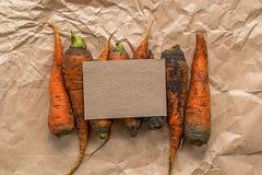 Papel en blanco con las zanahorias sucias en un papel arrugado Imagen de archivo