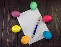 Papel en blanco con los huevos de Pascua en la tabla de madera Preparación para w Imagen de archivo libre de regalías