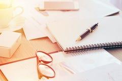 Papel en blanco del cuaderno, y documento borroso en la tabla de la oficina, concepto del informe de las finanzas del negocio de  Imagenes de archivo