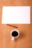 Papel en blanco, taza de café y pluma Foto de archivo libre de regalías