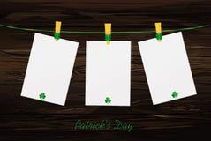 Papel en blanco tres con los tréboles verdes que cuelgan en una cuerda en una madera Fotografía de archivo