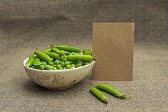 Papel en blanco y guisantes verdes Foto de archivo