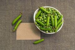 Papel en blanco y guisantes verdes en un cuenco Foto de archivo