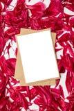 Papel en blanco y sobre con los pétalos rojos de las peonías en fondo gris foto de archivo libre de regalías