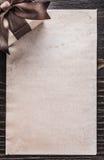 Papel encaixotado do presente na opinião do vertical da placa de madeira do vintage imagens de stock