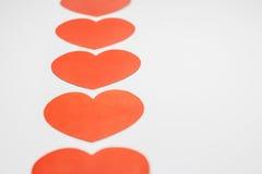 Papel formado como corazones en el fondo blanco Foto de archivo libre de regalías