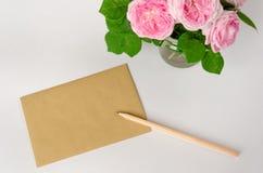 Papel hecho a mano marr?n de la hoja en blanco para el texto de saludo, un l?piz y las rosas rosadas en el fondo blanco Copie el  foto de archivo