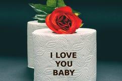 Papel higiénico blanco con la rosa del rojo en un fondo negro Imagen de archivo libre de regalías