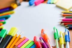 Papel, lápis coloridos, penas, marcadores e algum material da arte na tabela de madeira foto de stock