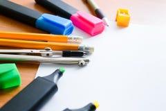 Papel, lápis coloridos, penas, marcadores e algum material da arte na tabela de madeira imagens de stock royalty free