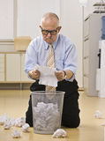 Papel masculino sênior da leitura no lixo. Foto de Stock