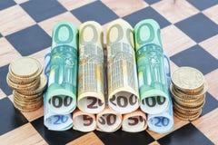 Papel moeda e moedas como o euro no tabuleiro de xadrez. fotografia de stock royalty free