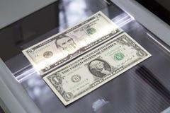 Papel moeda no varredor de vidro foto de stock royalty free