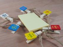Papel pegajoso amarelo com os clipes de papel de madeira como dias úteis Fotos de Stock Royalty Free