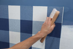 Papel pintado de la ejecución del decorador con la herramienta del trabajo en el movimiento Imagen de archivo libre de regalías