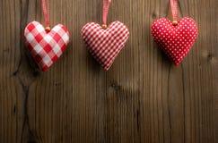 Papel pintado del día de tarjeta del día de San Valentín - corazones de la materia textil que cuelgan en la cuerda fotografía de archivo libre de regalías