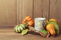 Papel pintado del otoño con la vela, las decoraciones de la calabaza y las hojas de la caída Tabla de la acción de gracias Imagen de archivo