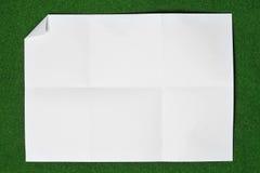Papel plegable y arrugado en hierba. Imagen de archivo libre de regalías