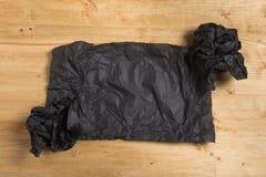 Papel preto enrugado com rolos de papel no fundo de madeira imagens de stock