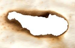 Papel quemado con el agujero Foto de archivo libre de regalías