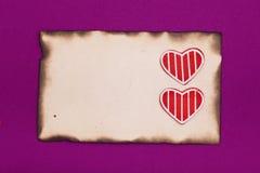 Papel quemado viejo y dos corazones Foto de archivo libre de regalías